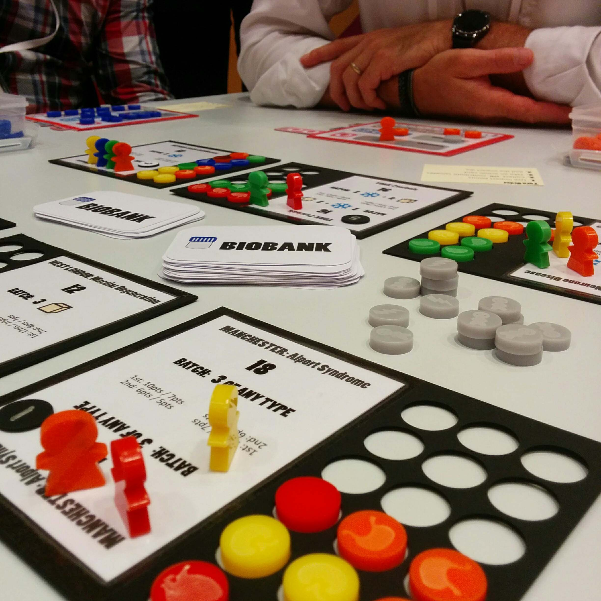 A black player board for a board game that is half filled with with red and yellow circular pieces. There are also red and yellow meeples on the board. A person's folded arms can be seen in the background.