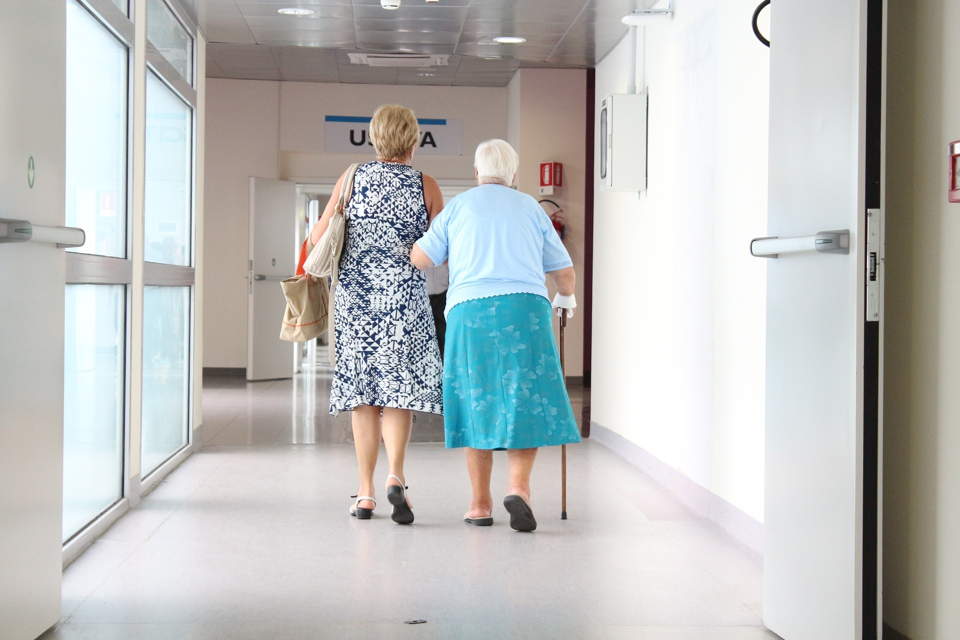 Two women walk, linking arms, down a hospital corridaor